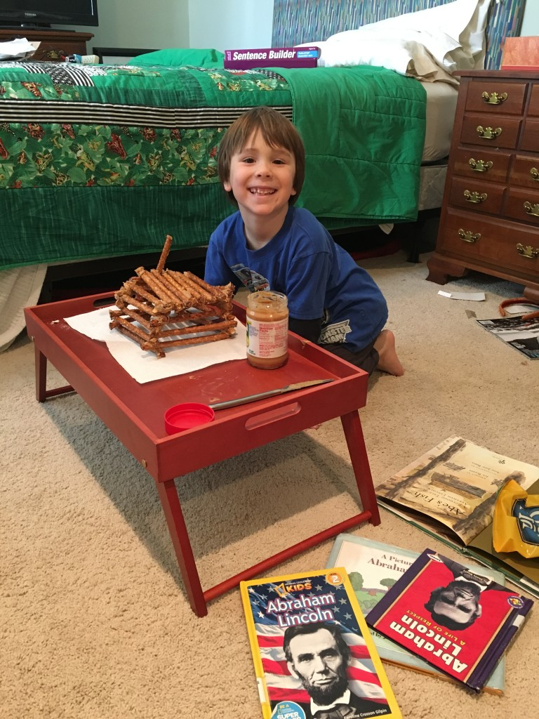 Creating a pretzel/peanut butter log cabin during our Presidents Unit Study